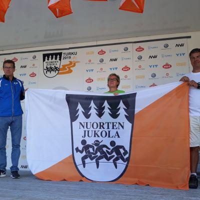 Kolme ihmistä pitää Nuorten Jukola -lippua käsissään.