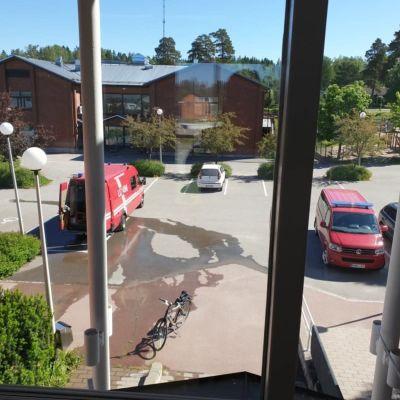 En stor vattenpöl på en parkeringsplats utanför en byggnad.