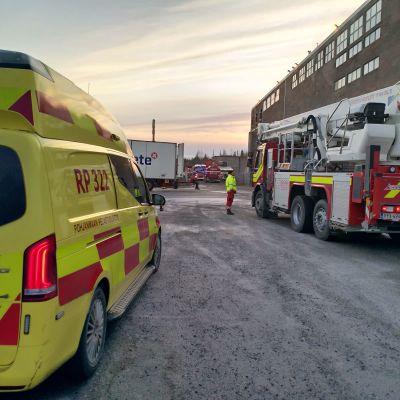 En ambulans och en brandbil står parkerade på gården till en industrihall.