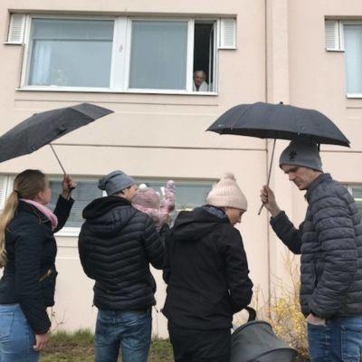 Personer utanför ett fönster där en äldre dam tittar ut.