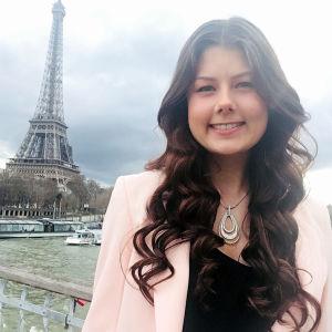 En kvinna med långt brunt hår som befinner sig i Paris. I bakgrunden syns Eiffeltornet.