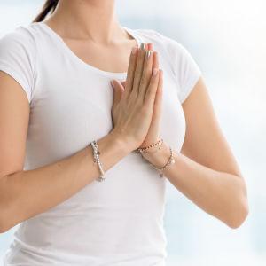 en kvinna i vit t-skjorta har händerna mot varandra