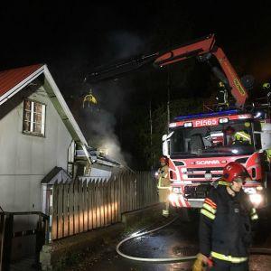Rök ligger omkring ett småhus, sn brandbil står intill det.