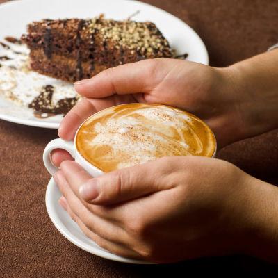 Händer håller om en kopp kaffe (cappucino)