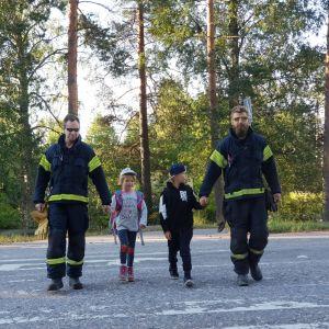 Två män i gula västar hjälper två barn, en flicka och en pojke, över ett övergångsställe.