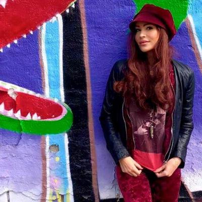 Sara Varga framför en färggrant målad vägg.