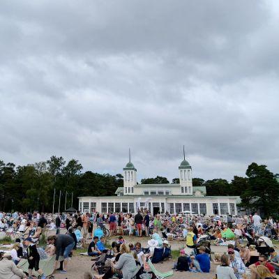 En bild på massor av människor som sitter på en strand och picknickar. I bakgrunden syns ett 1800-tals hus.