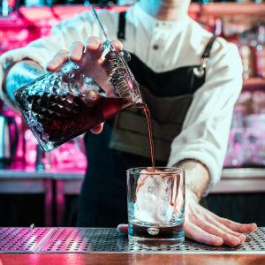 en barmästare blandar en drink som verkar ha något syrligt och isigt i sig