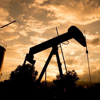 en oljeborr och en oljetank i skymning