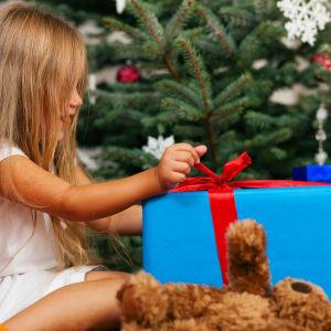 En liten flicka öppnar ett stort paket