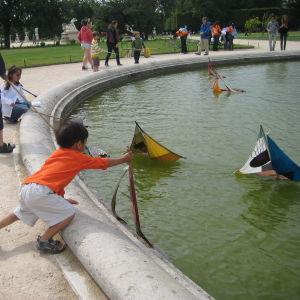 Lapset uittavat purjeveneitä pariisilaisen puiston vesialtaassa.