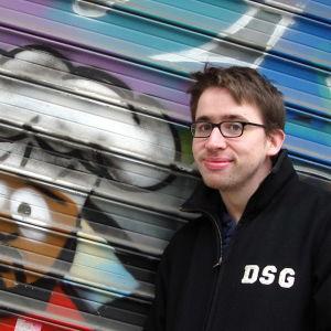 fredrik strage står leende mot en plåtvägg med en graffittimålning av karaktären chef från serien south park.