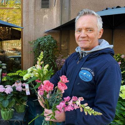 Man med blombukett i handen ler in i kameran. Blommorna är rosa och gröna. I bakgrunden står flera blommor uppradade.