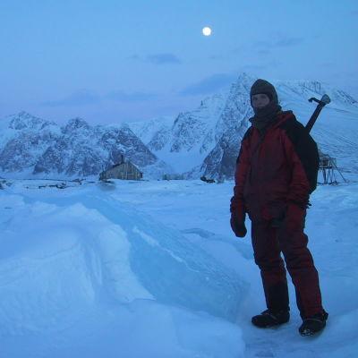 Priitta Pöyhtäri-Trøen napayössä Huippuvuorilla. Taivaalla loistaa kuu ja Priitalla on selässään kivääri jääkarhujen varalle.