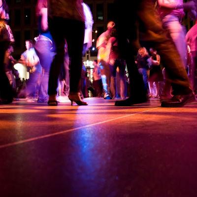 Alaviistosta kuvattu tanssilattia, jolla ihmiset tanssivat himmeässä valossa