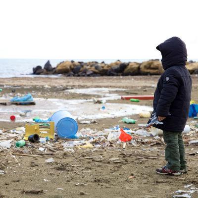 Barn står på nerskräpad strand.