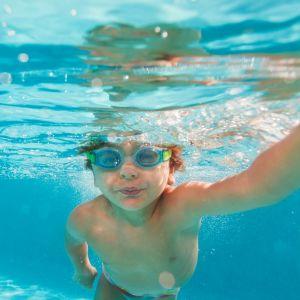 En pojke som simmar med simglasögon på