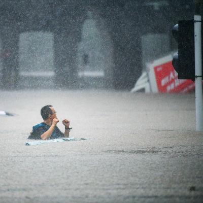 En man går på en översvämmad gata där vattnet når honom ända till bröstet. I bakgrunden en lastbil som fastnat i vattenmassorna.