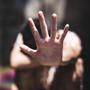 en kvinna visar stop med sin hand, handen i förgrunden, kroppen i bakgrunden