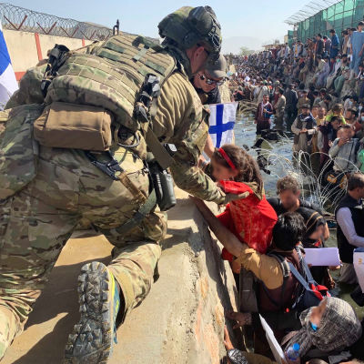 Finländska soldater hjälper människor på Kabuls flygplats.