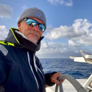 En man står på en båt iklädd solglasögon och en vindjacka. Han håller i ratten på segelbåten.