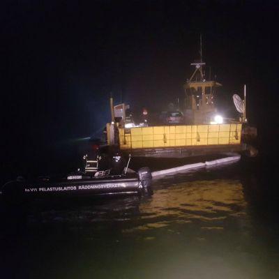 Den grundstötta färjan på en nattlig bild där man kan se en oljebom invid skrovet.