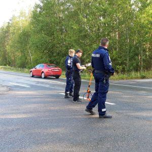 Poliser står vid sidan av en väg. På vägen står en röd bil.