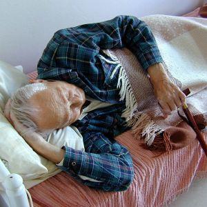 En gammal man vilar i en säng