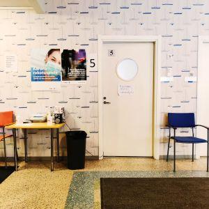 Rokotuspisteen odotushuone: ovi toimistoon.