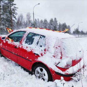 Auto ojassa Lehmon rampin lähellä Kuutostiellä. Ympärillä lunta.