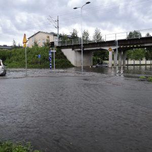 Katu lainehtii Rovaniemellä kirkon alikulun kohdalla, tiellä on autoja.