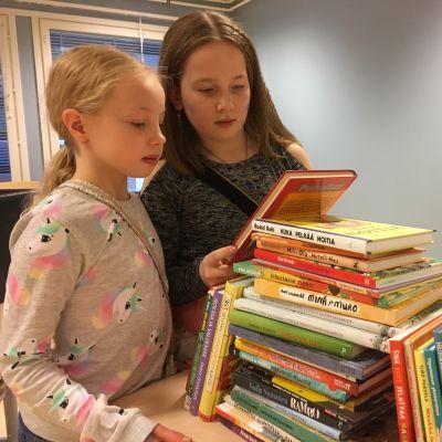 Neljäsluokkalaiset Iida ja Veera tutkivat vanhempainyhdistyksen kirjakeräykseen tulleita kirjalahjoituksia.