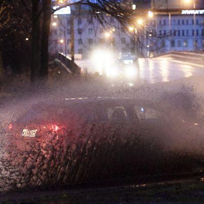 Auto ajaa vesilätäköstä ja aiheuttaa isot pärskeet ympäriinsä.