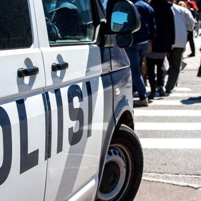 poliisiauto ja ihmisiä suojatiellä