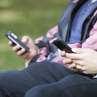 nuoria puiston penkillä kännyköiden kanssa