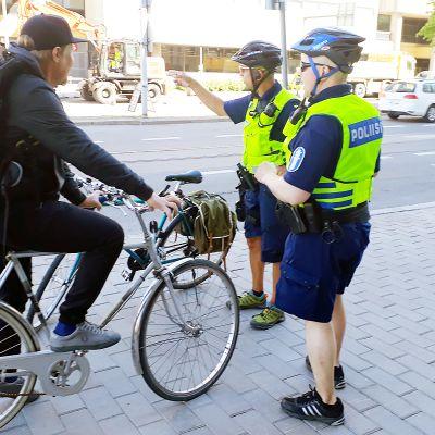 poliisit neuvomassa pyöräilijää