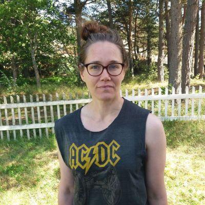 kvinna står på gräsplan vid staket med ac/dc skjorta