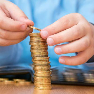 barnhänder staplar mynt