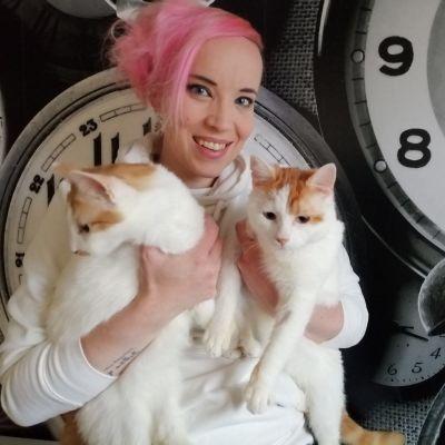 Nainen, jonka sylissä on kaksi kissaa.