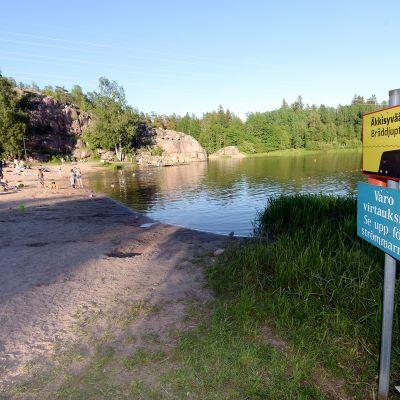 Pikkukosken uimarannalla varoituskylttejä ja pelastusrengas