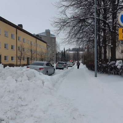 Kuva Jyväskylässä kadulta, jossa on iso lumikasa. Kadun varrelle on pysäköity henkilöautoja.