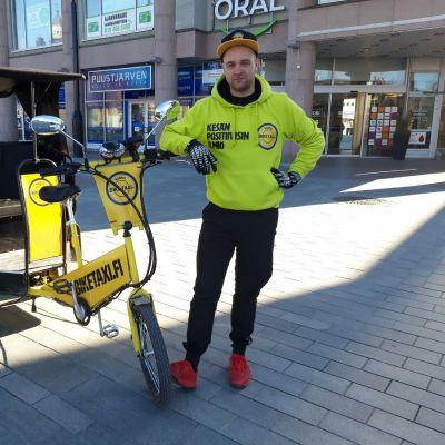 Biketaxin yrittäjä Miika Keihänen polkupyörätaksinsa vieressä Kuopion keskustassa.