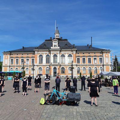 Mielenosoittajat seisovat Kuopion kaupungintalon edessä.