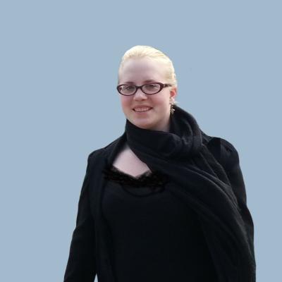 Vaaleahiuksinen, silmälasipäinen, mustaan pukeutunut nainen hymyilee puolikuvassa, tausta on harmaa.