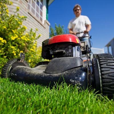 En man som klipper gräs.