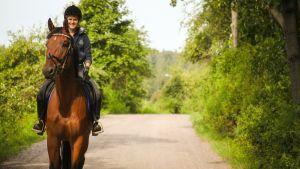 Nainen ratsastaa tiellä