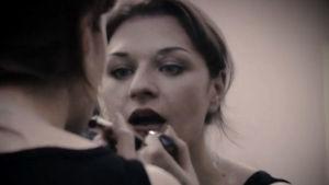 Nuori nainen laittaa huulipunaa. Kuva dokumentista Suomi on kaunis sana (2004).