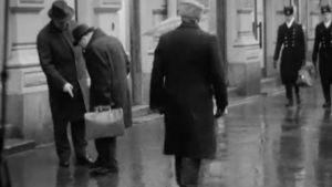 Miehet kummastelevat kolikkoa kadulla.