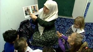 Isra Lehtinen opettaa lapsia dokumentissa Pohjantähden alla: Allahin nimeen (1998)