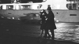 Siviilipukuinen huoltopoliisi ohjaa laivatyttöä pois satamasta Helsingissä 1960-luvulla.